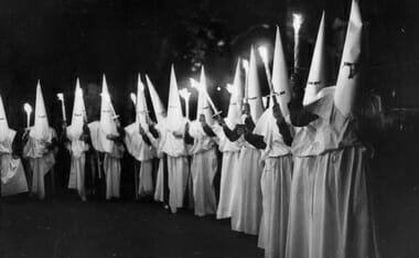 6th October 1951:  A Ku Klux Klan (KKK) procession at the Festival Pleasure Gardens in Battersea Park, London, celebrating the 1951 Festival of Britain.  (Photo by Keystone/Getty Images)